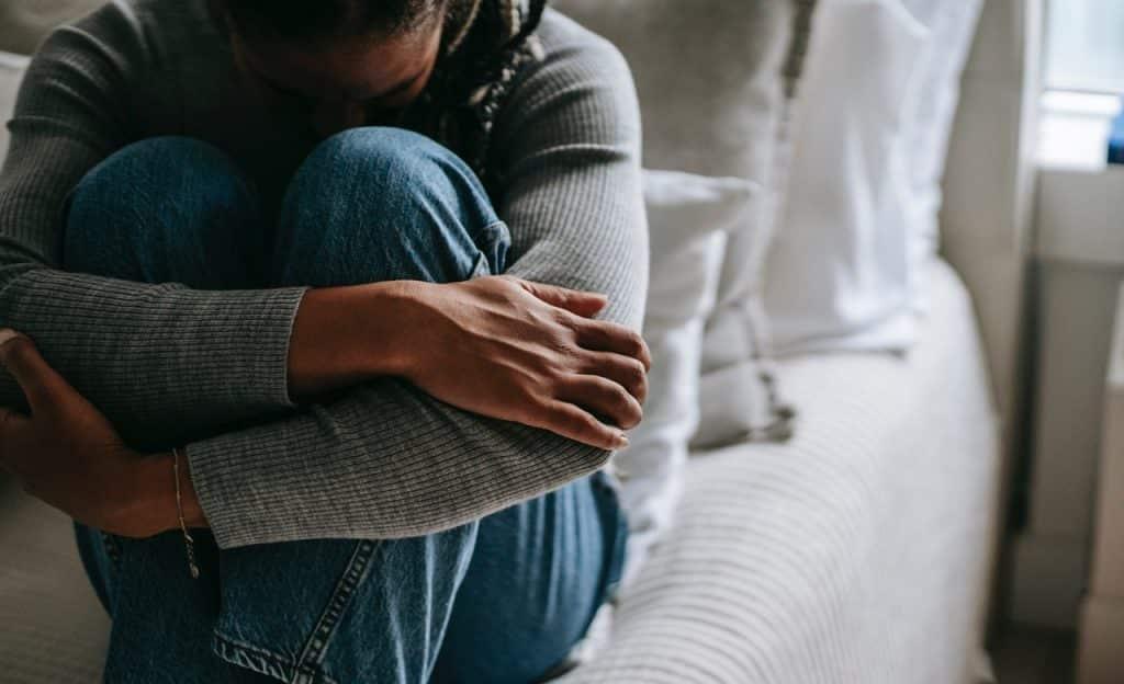 Mulher sentada em uma cama chora e abraça as próprias pernas.