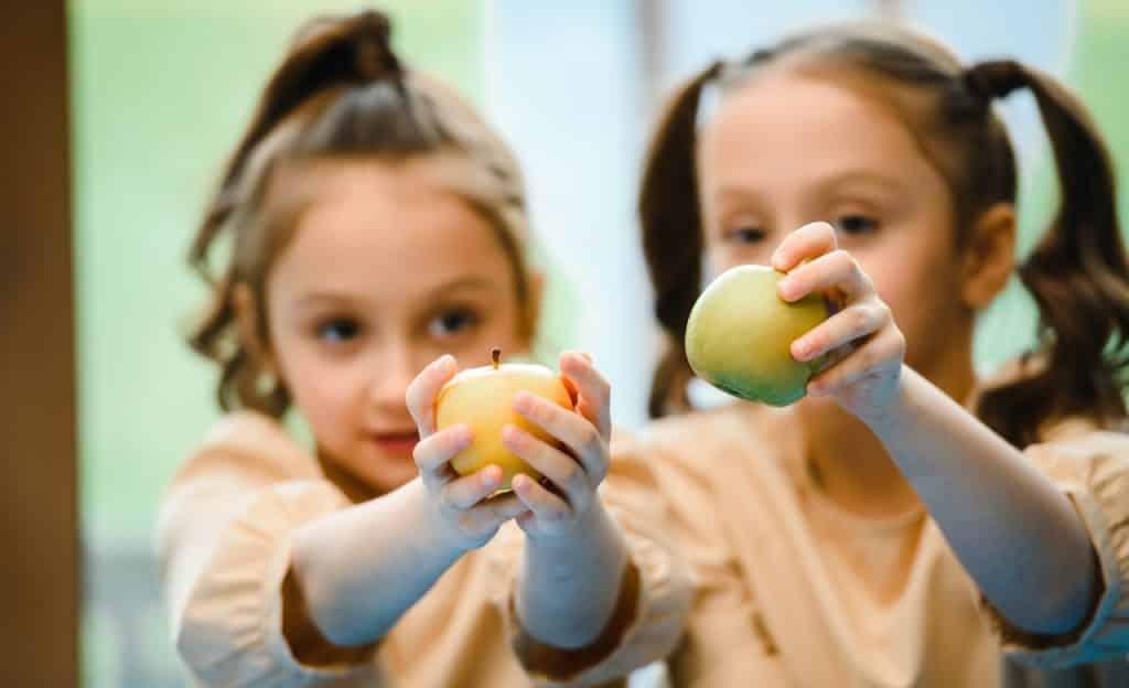 Duas meninas seguram maçãs.