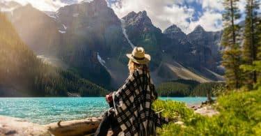 Mulher sentada próxima de um lago.