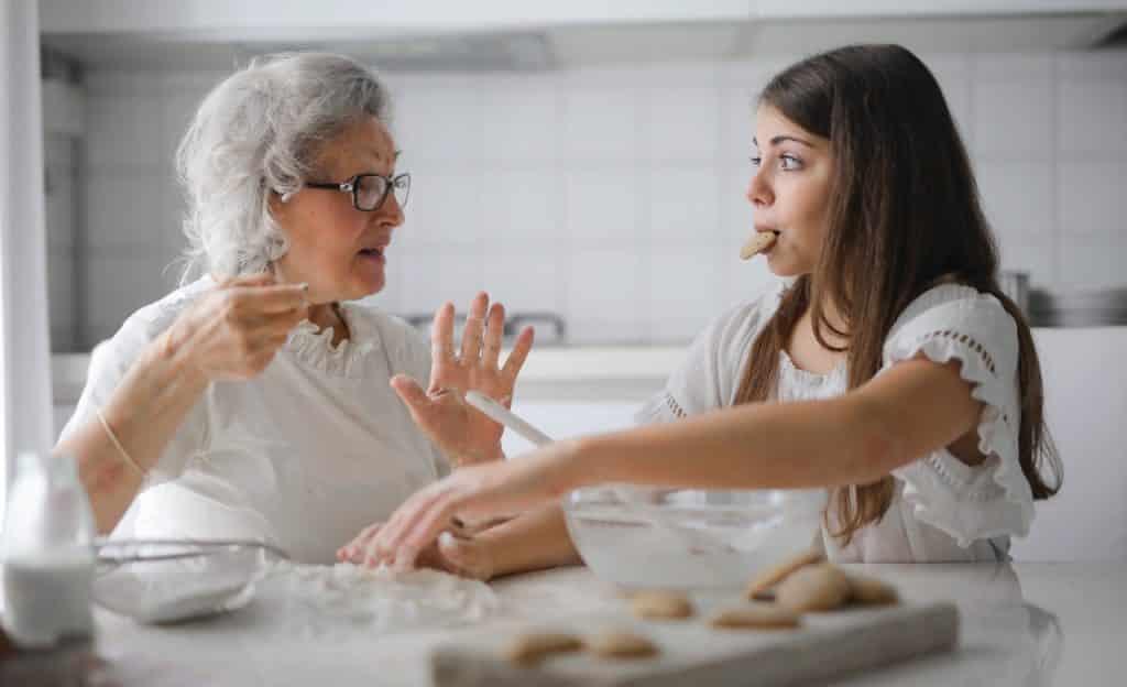 Uma menina e sua avó fazem biscoitos. As duas estão sentadas à bancada e olham uma para a outra.