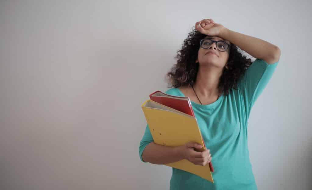 Mulher carrega duas pastas grandes em um braço. O outro está sobre sua testa. Ela olha para cima e tem o semblante aflito.