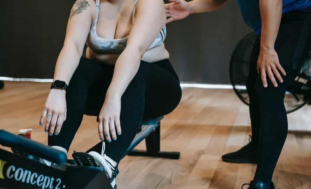 Mulher pratica exercício físico em academia.