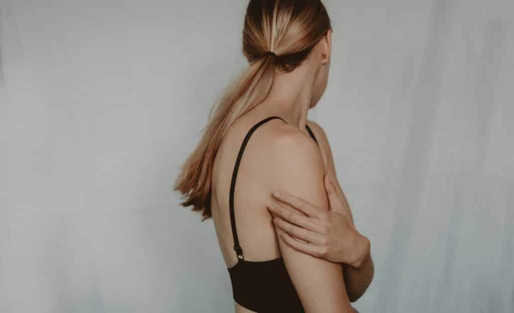 Mulher abraça a si mesma e olha para trás.
