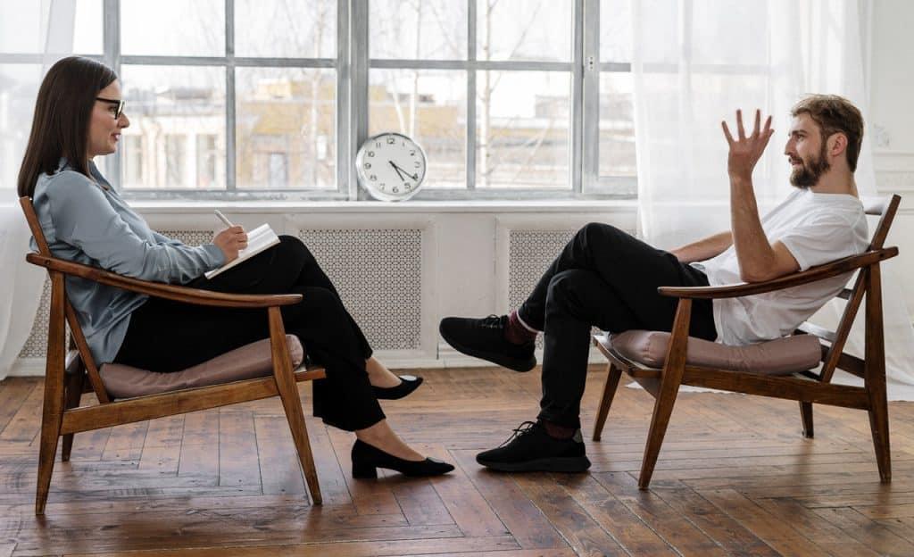 Homem e mulher sentados em cadeiras. Eles estão em uma sessão de terapia.