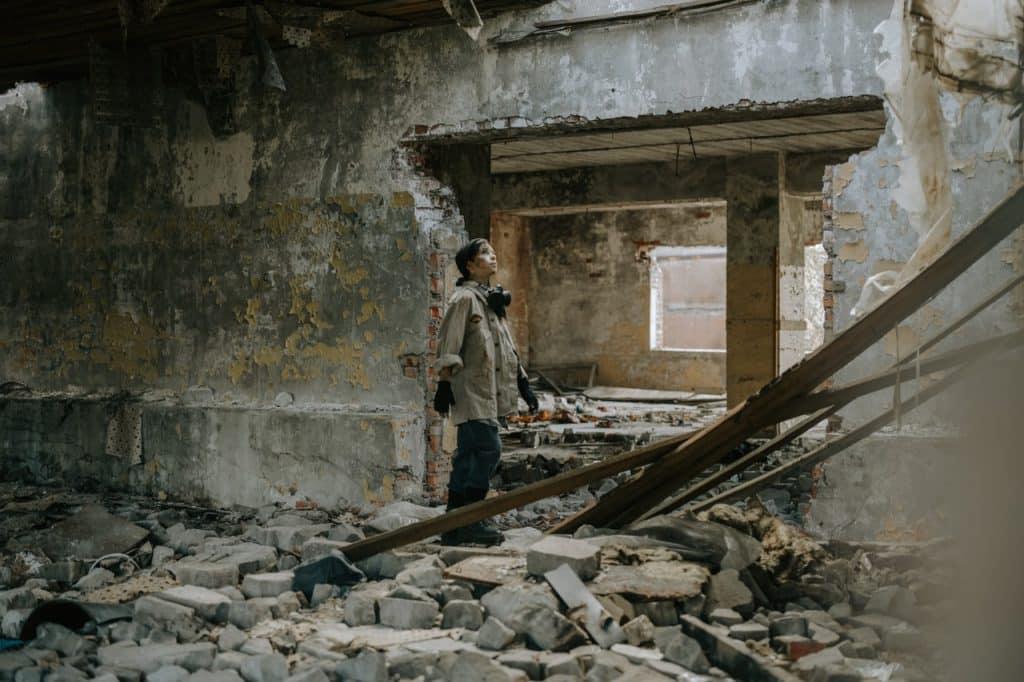 Menino olhando para cima em meio aos escombros de um prédio demolido.