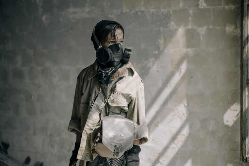 Menina com uma máscara de respiração em uma casa meio demolida.