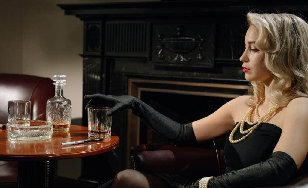 Mulher sentada em poltrona segura um copo de whiskey.