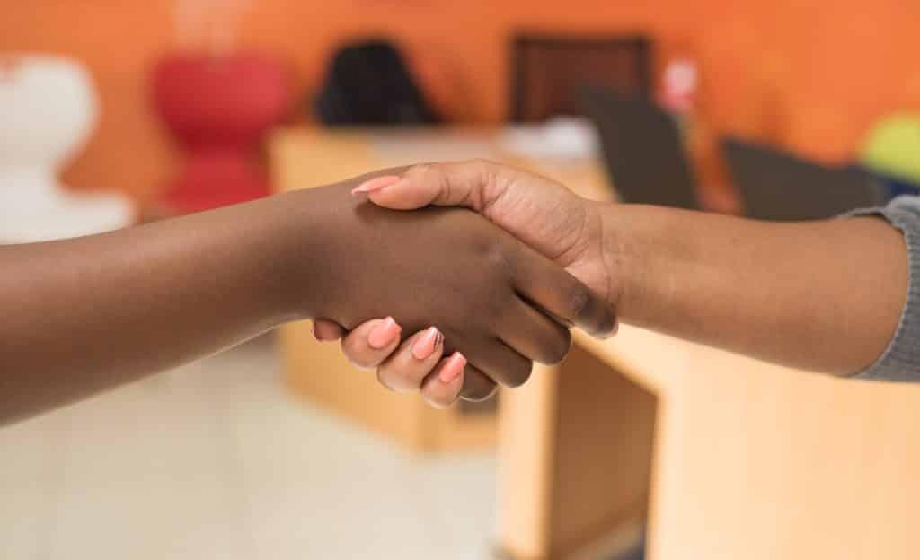Duas mulheres apertam as mãos.