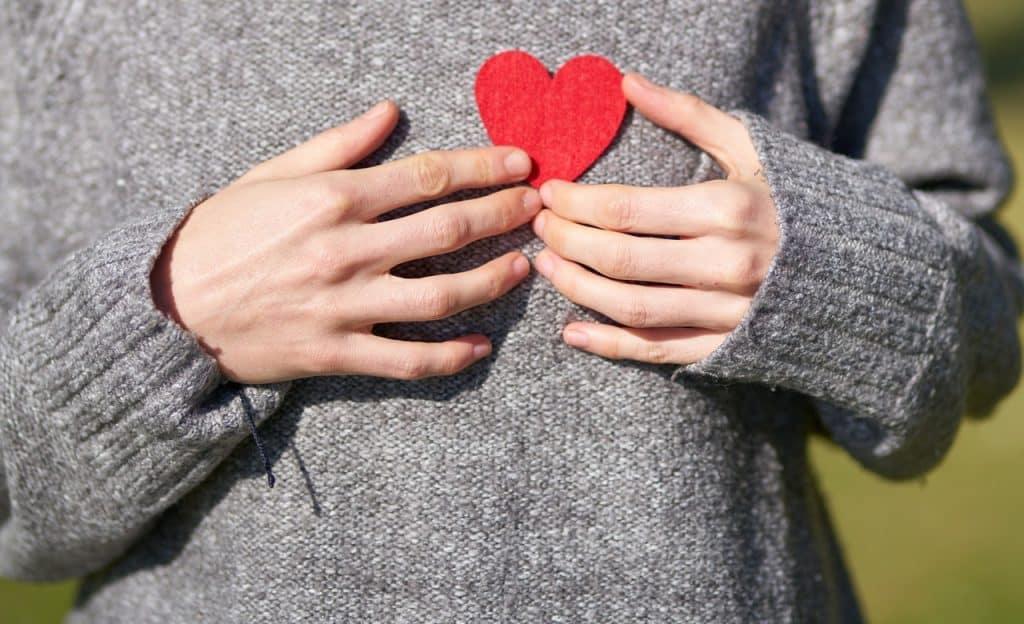 Mulher segurando um coração vermelho de papel próximo ao peito.