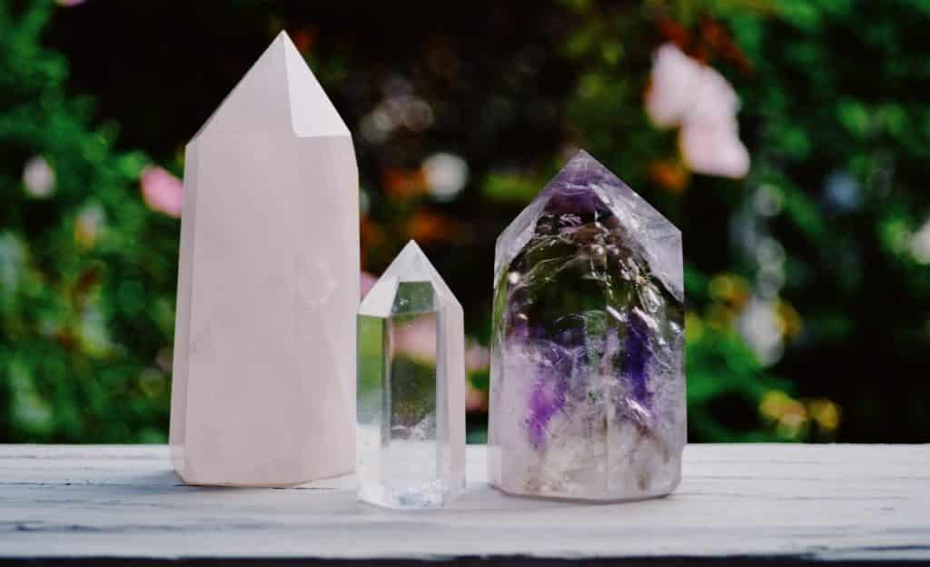 Três cristais sobre superfície de madeira. O ambiente é externo.