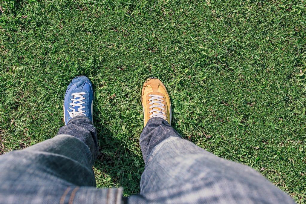 Homem calçando tênis de cores diferentes