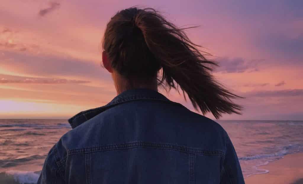 Mulher observa mar. Seu cabelo está preso em um rabo de cavalo e ao vento.
