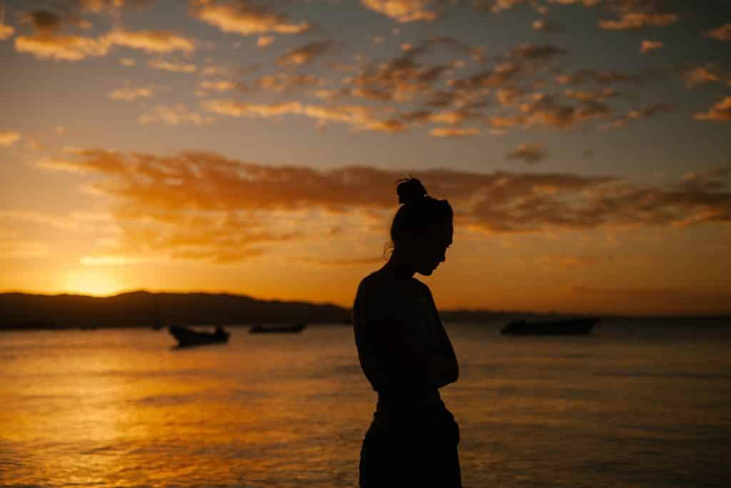 Mulher cabisbaixa em cenário externo. Há uma praia e o pôr do sol.