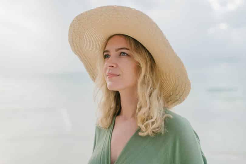 Mulher branca loira com chapéu na cabeça.