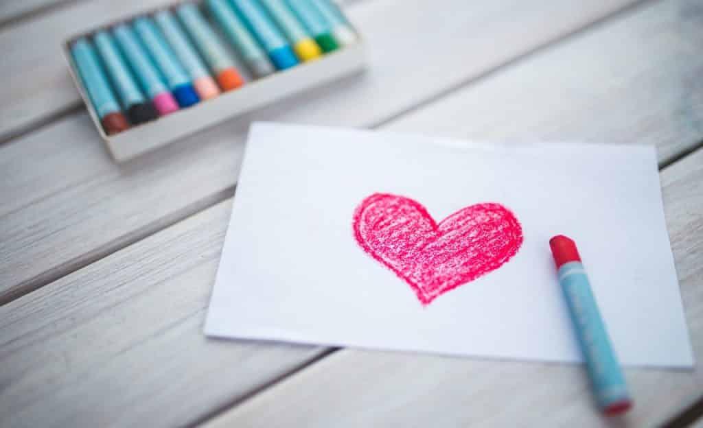 Coração desenhado em folha de papel sobre superfície de madeira clara. Ao lado há uma caixa de giz de cera.
