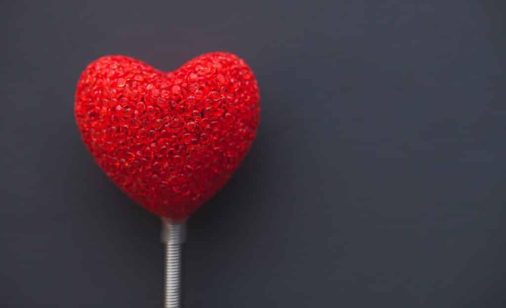 Coração vermelho posto em estrutura fina metálica. Ele está sobre um fundo cinza.