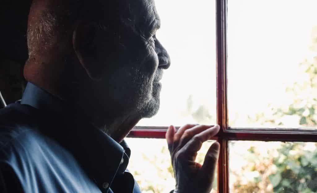 Homem idoso observa o ambiente externo através da janela.
