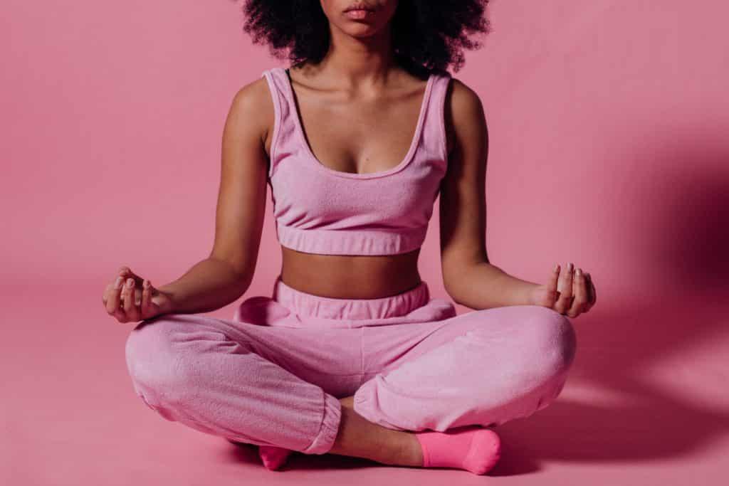Mulher de roupa rosa meditando em um espaço da cor rosa