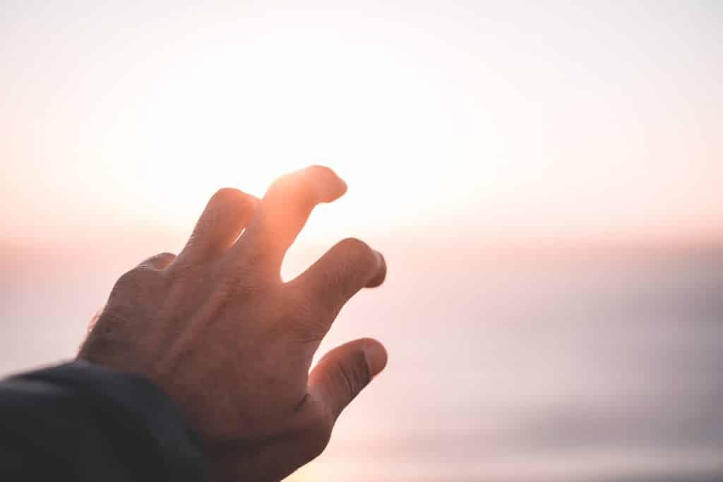 Mão de frente ao pôr do sol