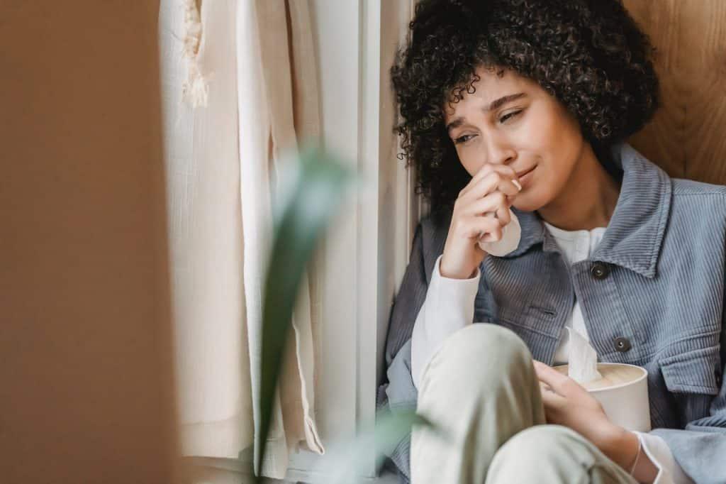 Mulher encostada na parede, chorando, com uma caixa de lenços de papel nas mãos.