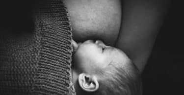 Imagem em preto e branco de um bebê sendo amamentado pela mãe