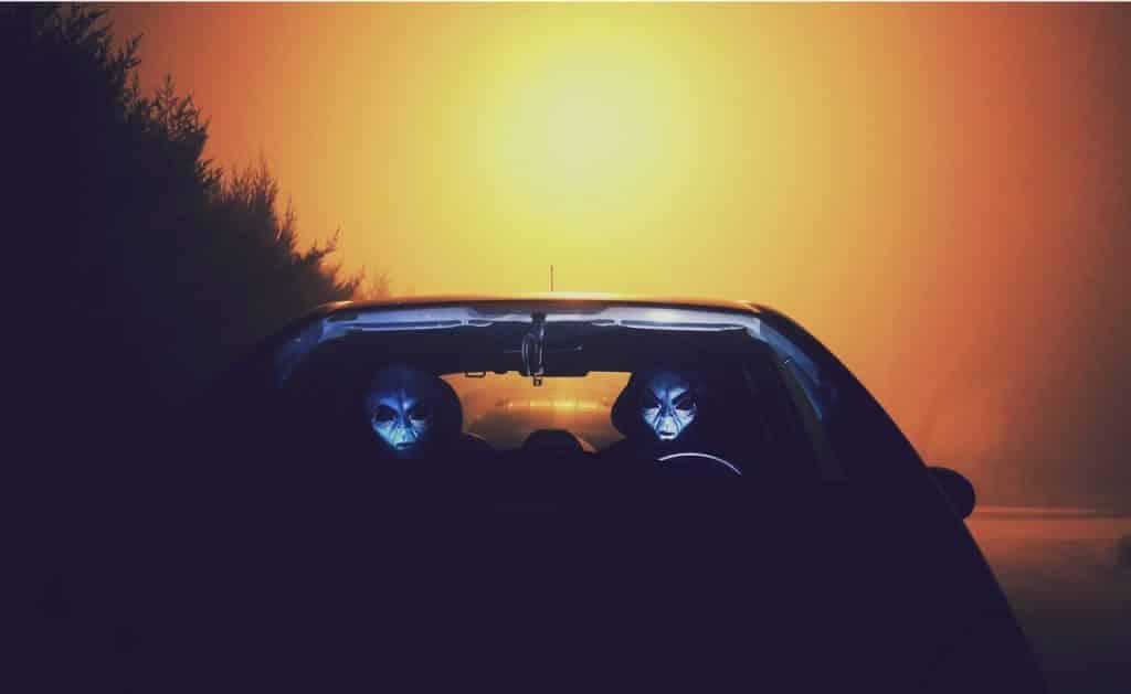 Dois homens mascarados de alienígenas sentados em um carro.