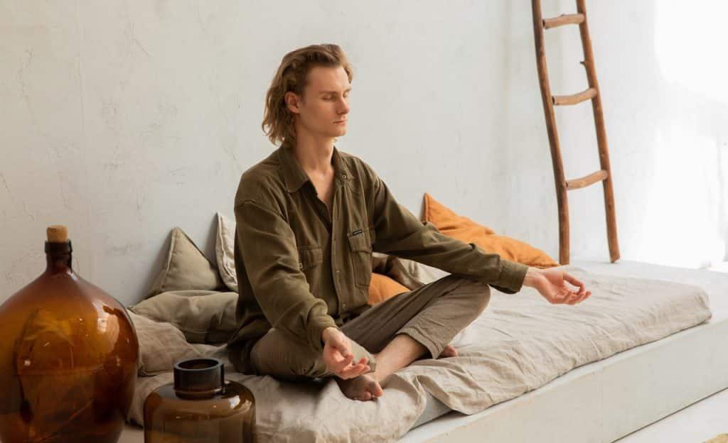Homem em prática meditativa em ambiente interno.