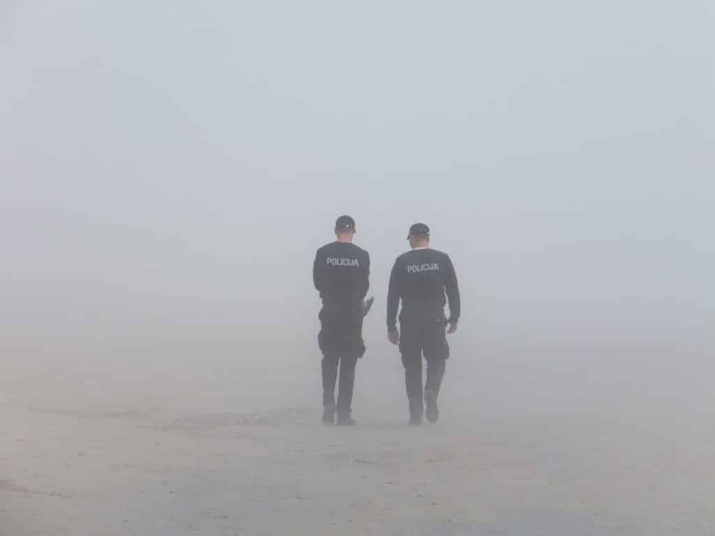 Dois policiais caminhando em um lugar com névoa.