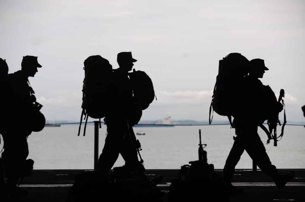 Silhueta de soldados carregando suas malas e armas.