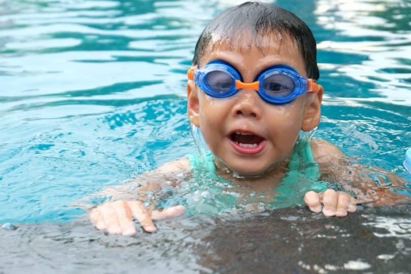 Criança em uma piscina com óculos de proteção