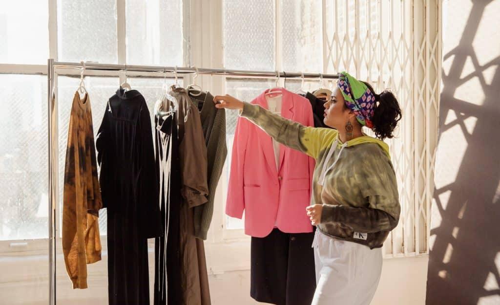 Mulher arrumando roupas no cabide.