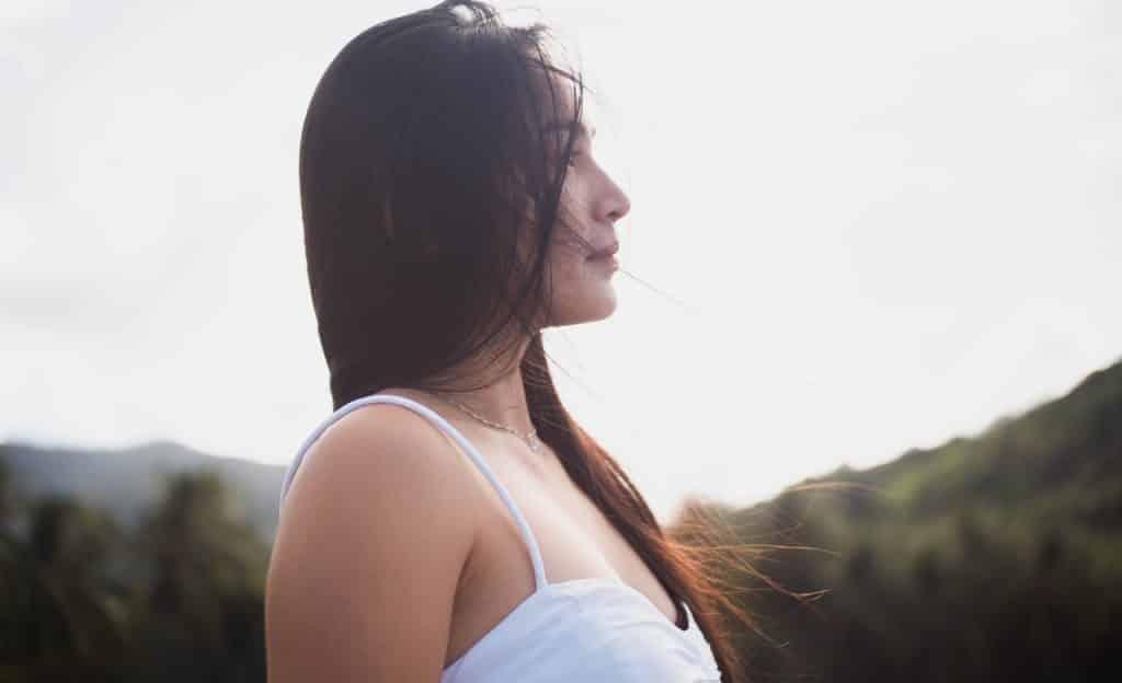 Mulher observa ponto aleatório ao horizonte. O cenário é externo e seus cabelos estão ao vento.