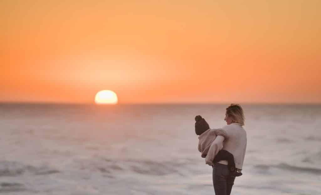 Mulher carrega criança. O cenário é de pôr do sol.