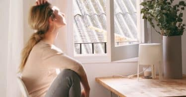 Mulher sentada à janela.