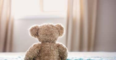 Urso de pelúcia em cima de uma cama de frente para uma janela iluminada