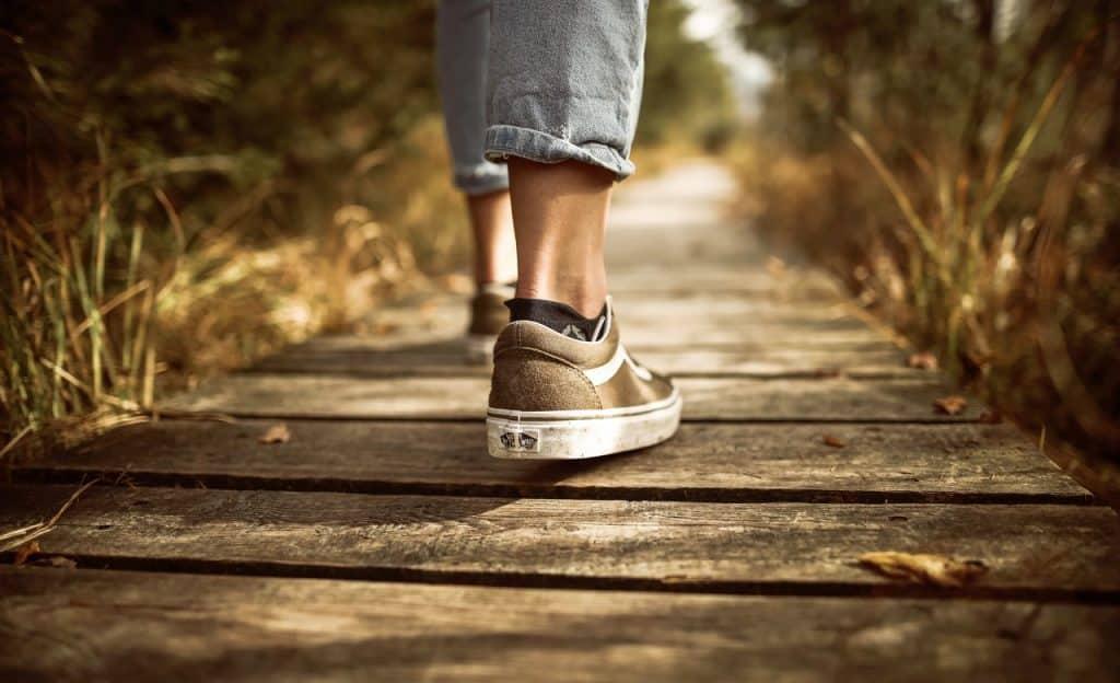 Pés caminham por estrutura de madeira.