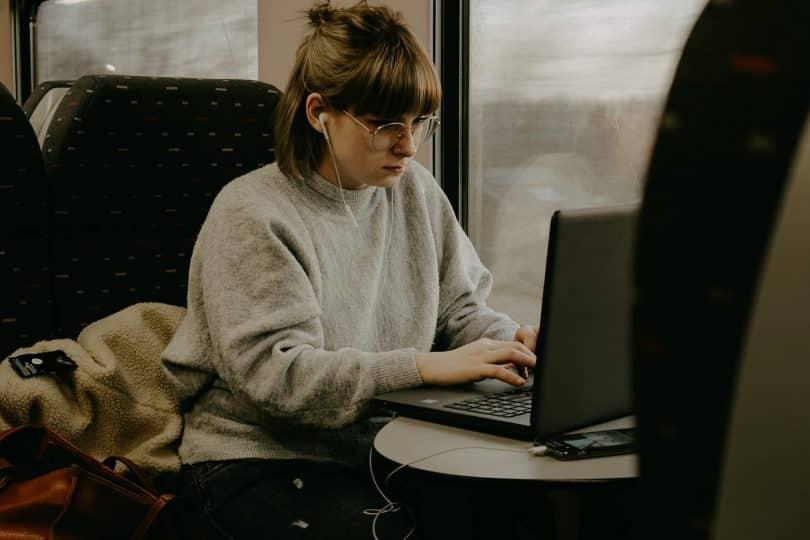 Mulher branca trabalhando num notebook.