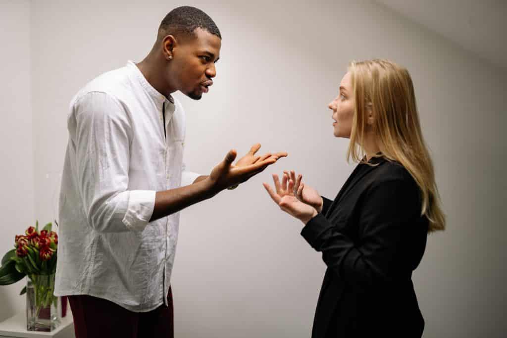 Um homem apontando o dedo na cara de uma mulher e brigando com ela
