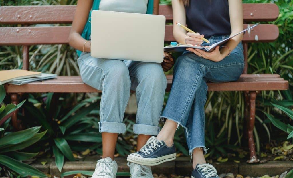 Duas mulheres estudam juntas em um banco de praça. Uma, à direita, está com um notebook sobre as pernas, enquanto a outra segura um caderno e escreve nele.