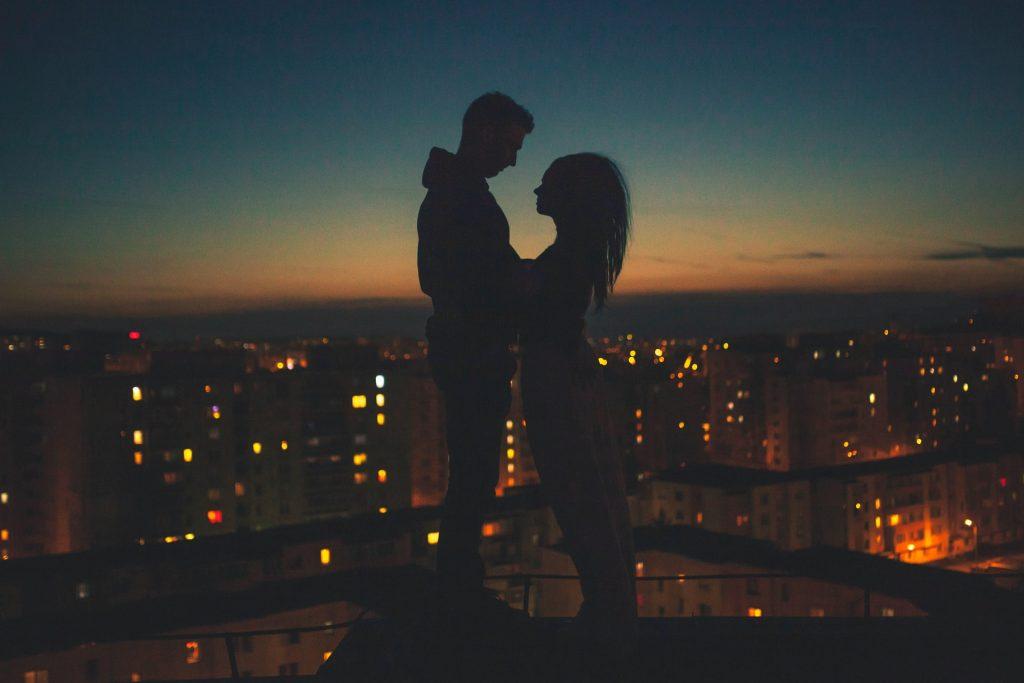 Silhueta de homem e mulher frente a frente em cima de um prédio.