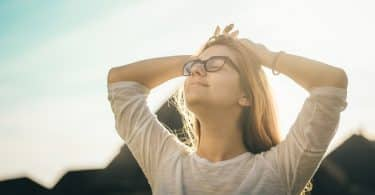 Mulher branca de óculos fechados e braços na cabeça.