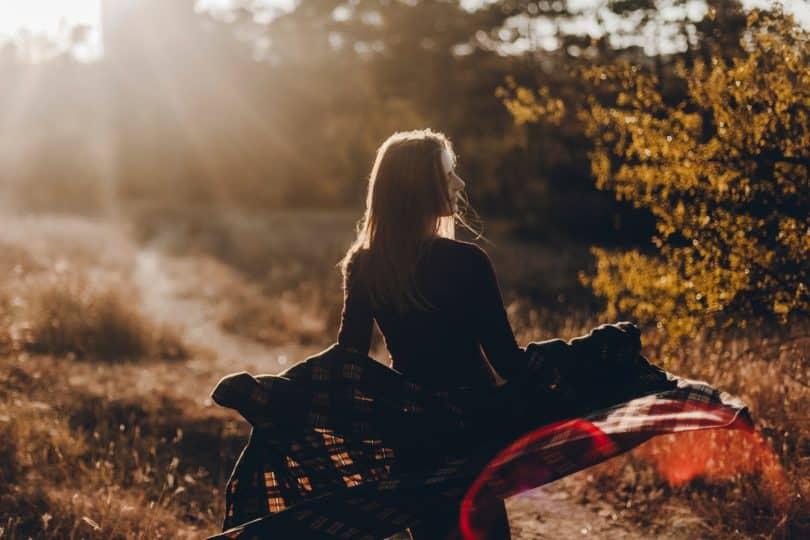 Mulher de costas em um campo.