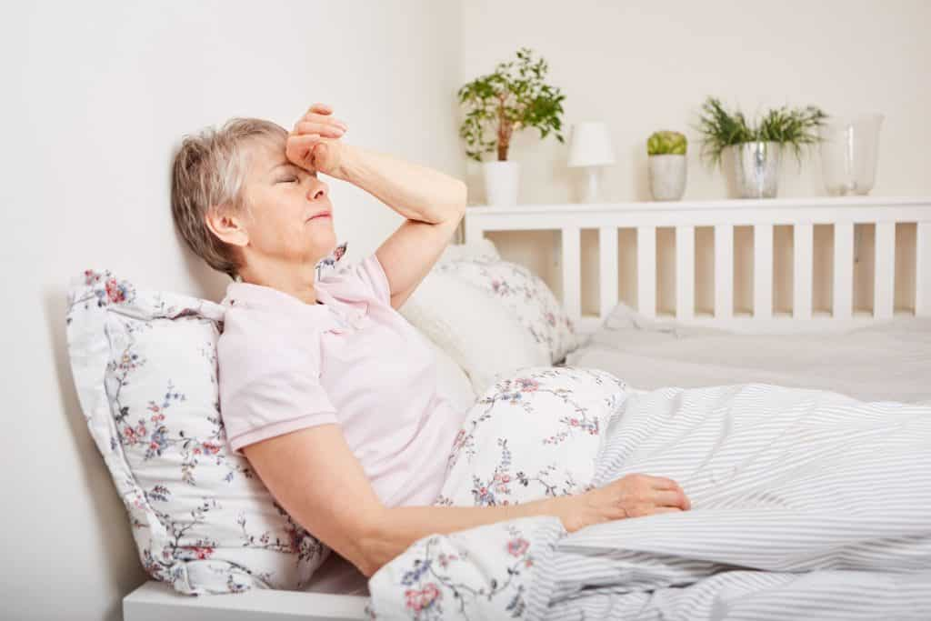 Mulher idosa com doença deitada na cama