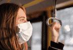 Mulher de máscara olhando pela janela do ônibus
