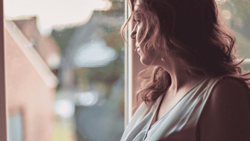 Mulher olhando pensativa para a janela