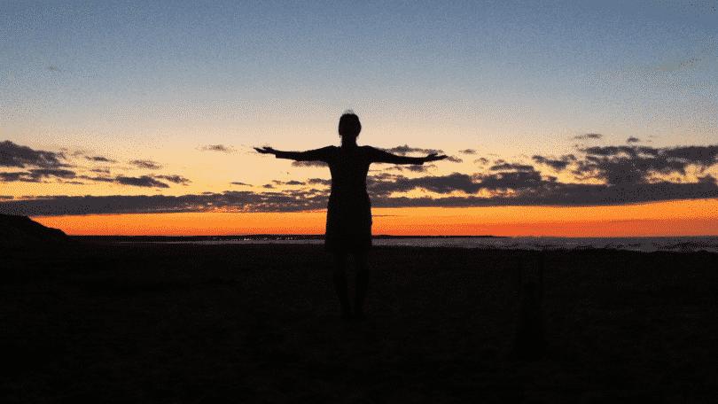 Silhueta de pessoa de braços abertos observando o por do sol