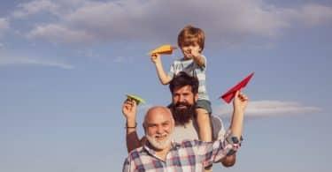 Três diferentes gerações conceituadas a partir de três pessoas: um homem idoso à frente, logo atrás dele um jovem adulto e, sobre os seus ombros, um menino. Os três têm aviões de papel nas mãos.