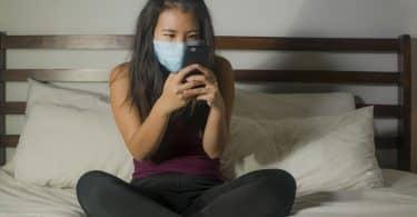 Mulher sentada em cama mexe em celular. Ela veste uma máscara azul no rosto.