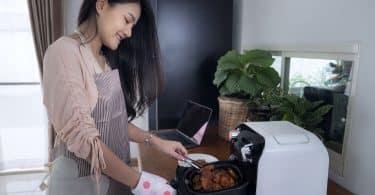 Mulher fritando frango em uma fritadeira elétrica.