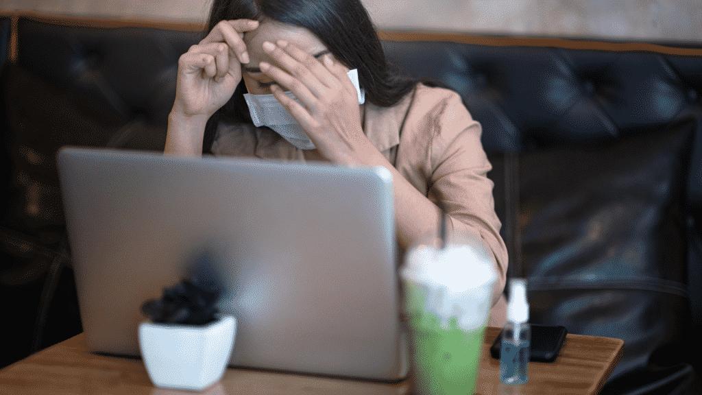 Mulher de máscara estressada em um café